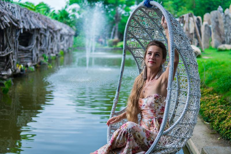 Beautiful brunette in dress swinging on a swing over the water in the Park in Sunny day royalty free stock photography
