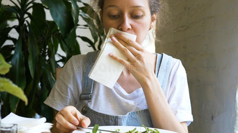 Beautiful brunette eats green fresh salad and wipes mouth royalty free stock photo