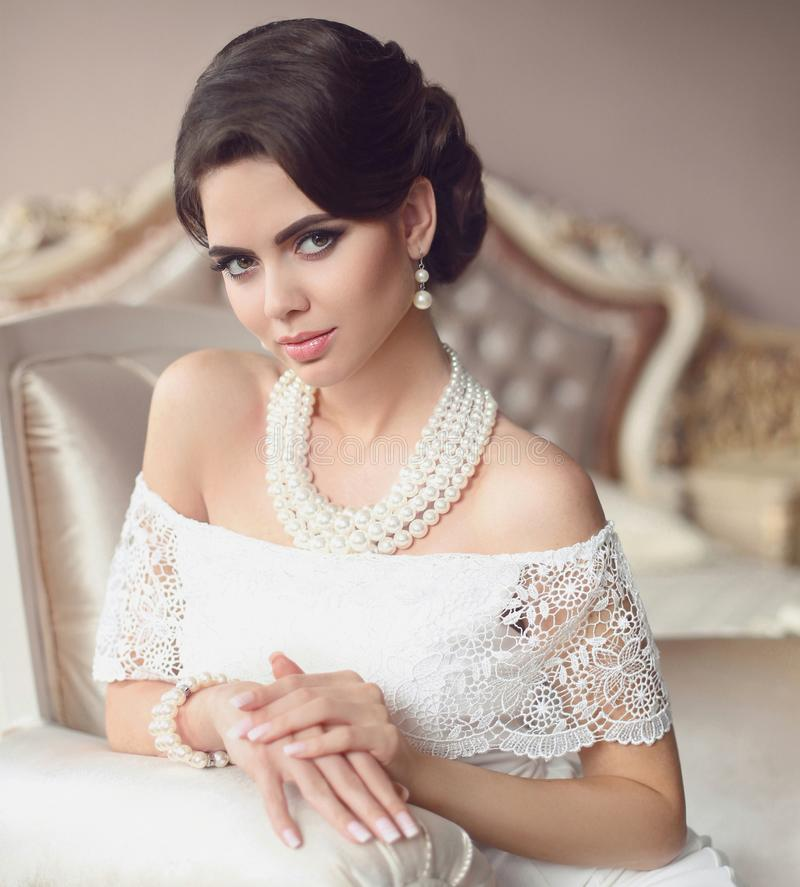 Beautiful brunette, elegant woman portrait. Fashion pearl jewelry set. Retro lady with makeup, wavy hairstyle in white dress stock image