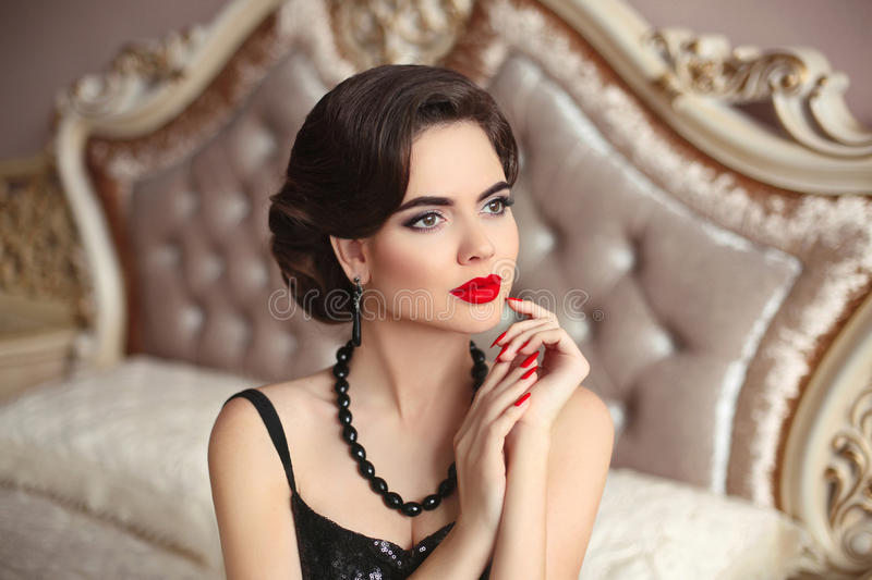 Beautiful brunette, elegant woman portrait. Manicure nails. Retro lady with red lips makeup, wavy hairstyle posing on modern bed royalty free stock images
