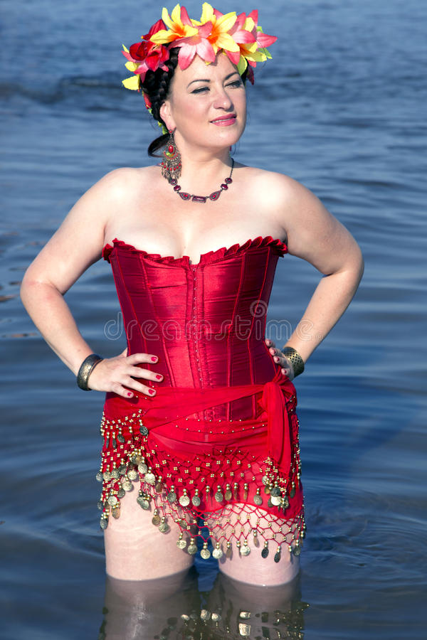 Beautiful woman in a red corset and floral chaplet stock photo