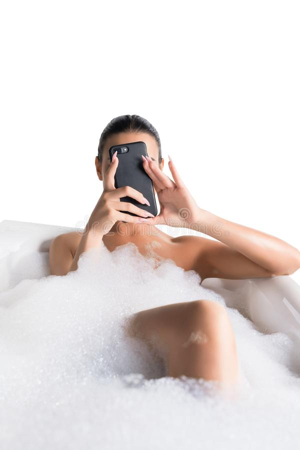 Beautiful brunette in foam bath with phone stock photo
