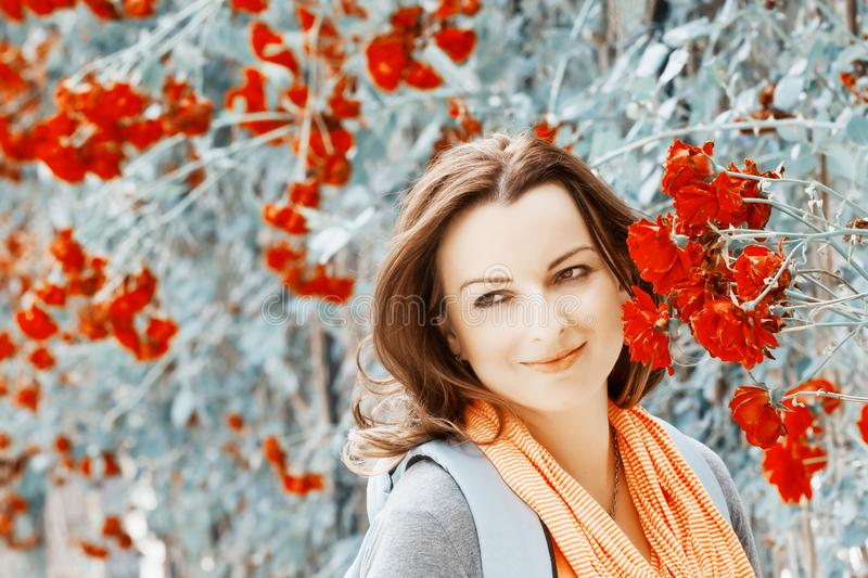 Young woman in garden under red roses bower royalty free stock images