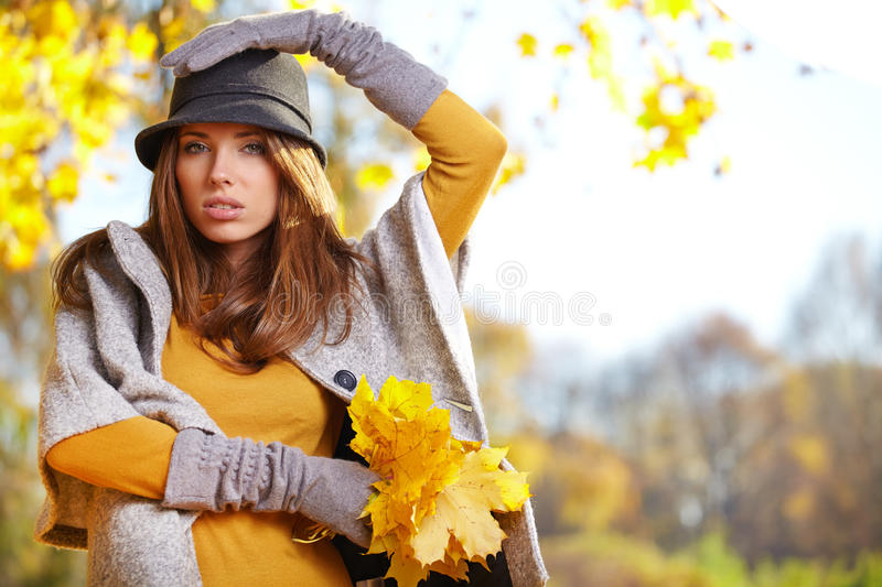 Beautiful brunette girl in autumn park. Warm sunny da royalty free stock image