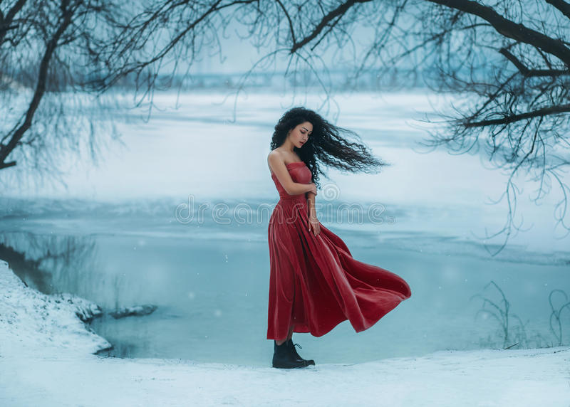 Beautiful brunette girl. Badly frozen. Background shore of a frozen river, water and ice. She is dressed in a beautiful red dress. Sad face, the wind waves are
