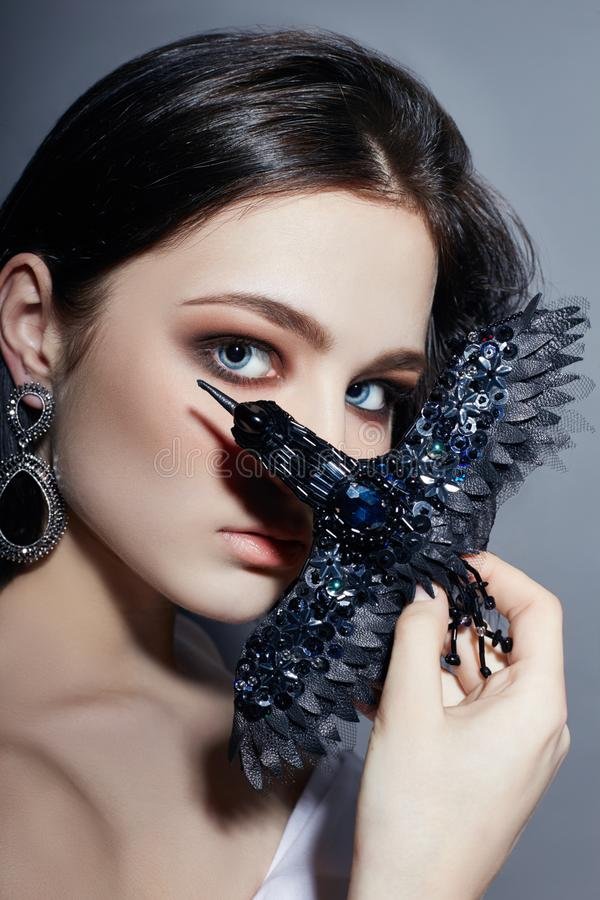 Beautiful brunette girl with big blue eyes holding a black brooch decoration in the form of birds. Fashion portrait natural stock photos