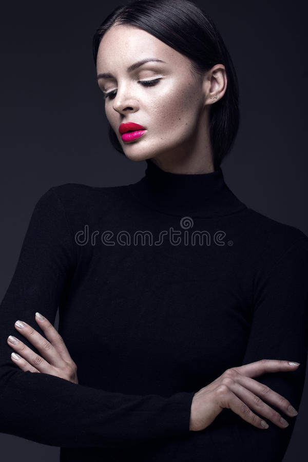 Beautiful brunette girl in a black dress, straight hair and trendy makeup. Glamour beauty face. royalty free stock image