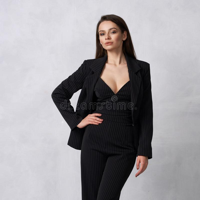 Beautiful brunette girl in black striped jumpsuit and blazer royalty free stock photography