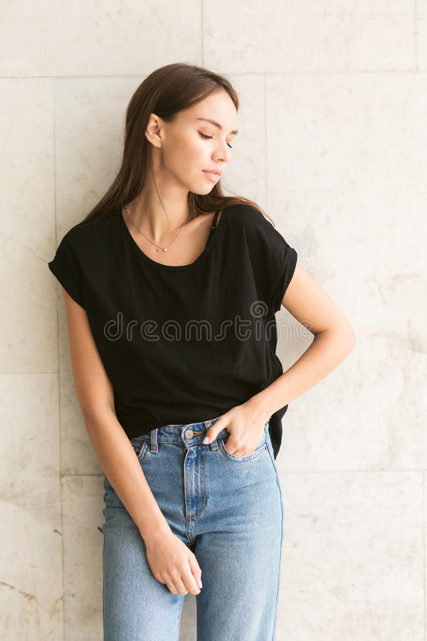 Beautiful brunette girl in a black T-shirt and mom jeans on the street. Beautiful brunette girl in black T-shirt and mom jeans on the street royalty free stock images