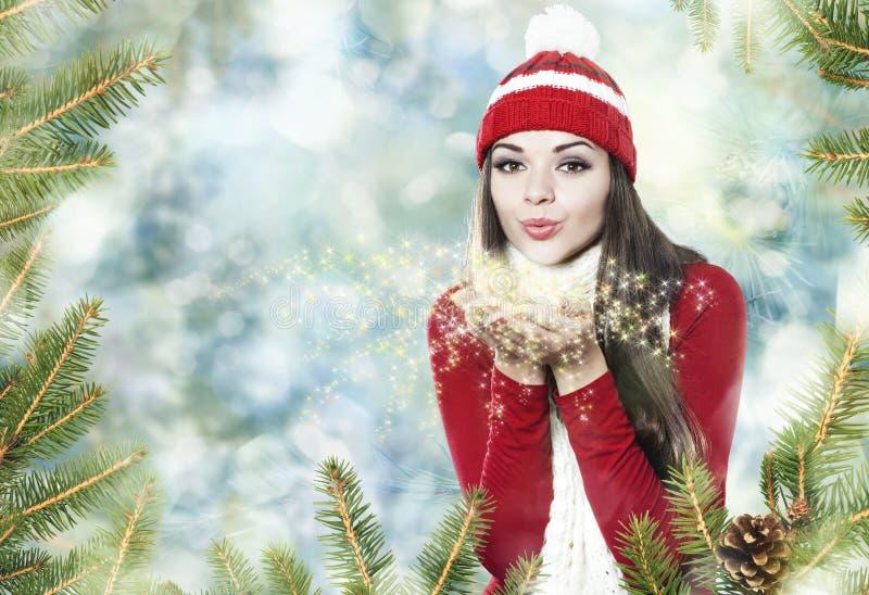 Beautiful brunette girl blowing star dust - christmas portrait stock photos