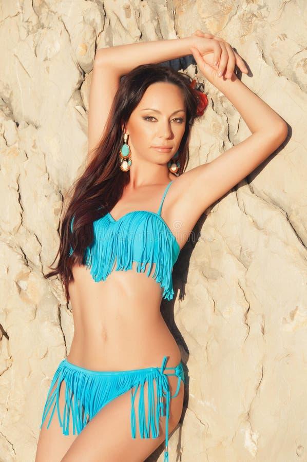 Beautiful brunette girl in blue bikini posing royalty free stock image