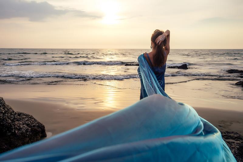 Beautiful brunette girl in blue gray chameleon dress with long train sitting on a beach at amazing sunset. woman in chic. Outfit near a rock on a tropical royalty free stock photography