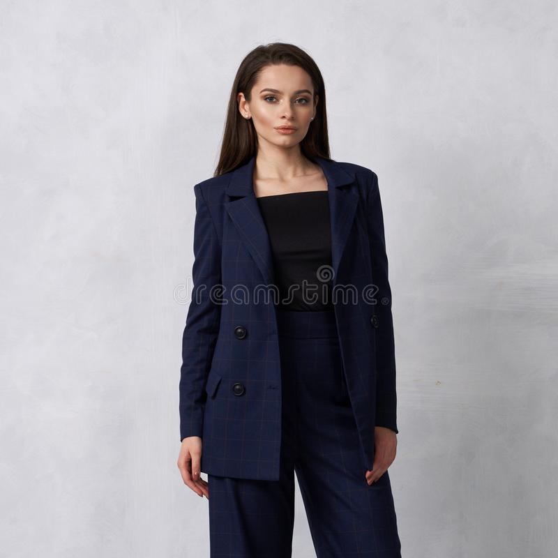 Beautiful brunette girl in blue squared jumpsuit and blazer royalty free stock photo
