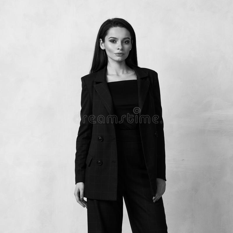 Beautiful brunette girl in blue squared jumpsuit and blazer royalty free stock images