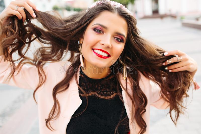 Beautiful brunette girl with bright make up holding her hair and smiling at camera. royalty free stock images