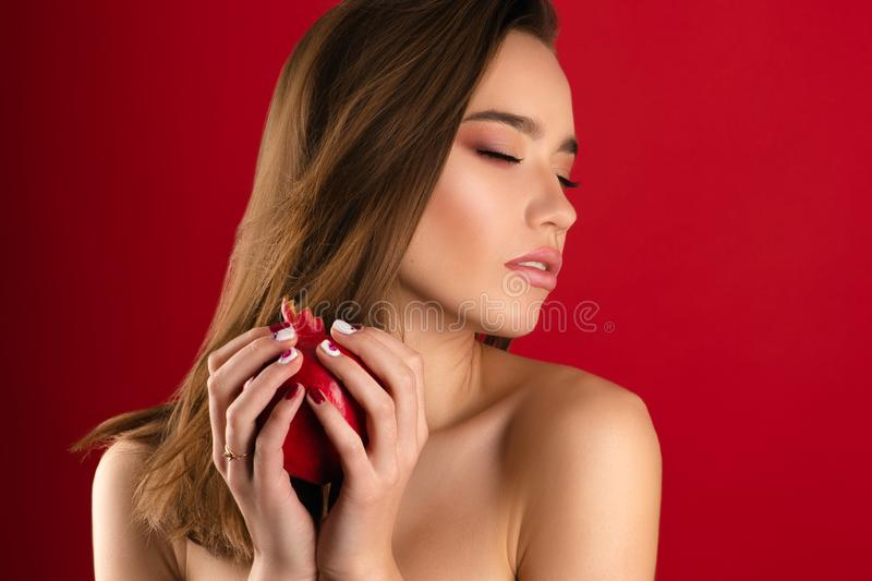 Beautiful brunette girl with bright makeup with pomegranate stock photos