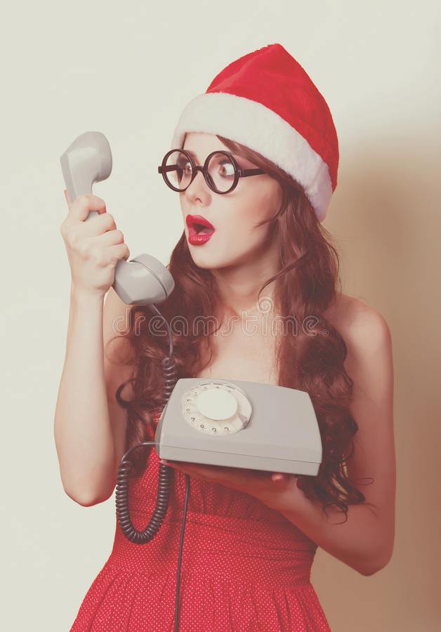 Beautiful brunette girl in christmas hat with telephone on yellow background. royalty free stock photography