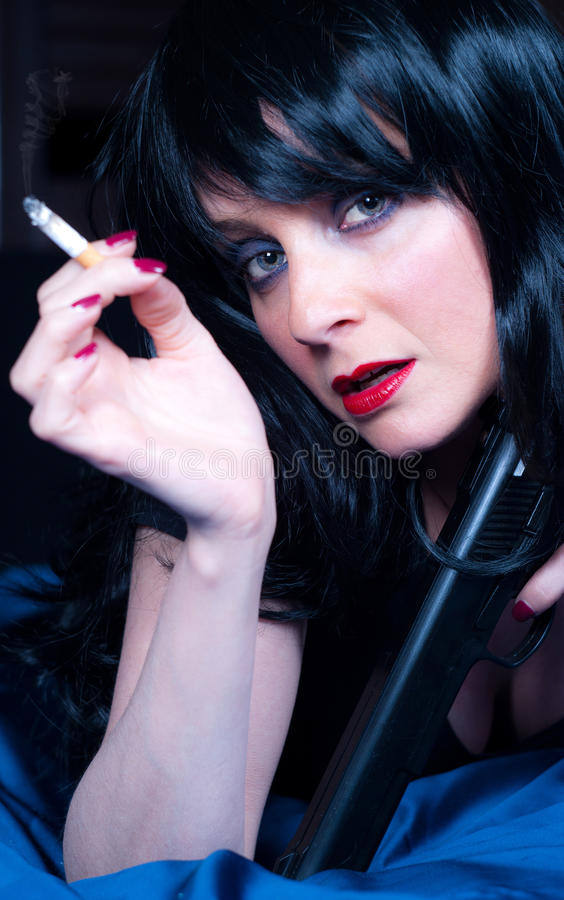 Beautiful Brunette Girl With Cigarette And Gun Stock Photo