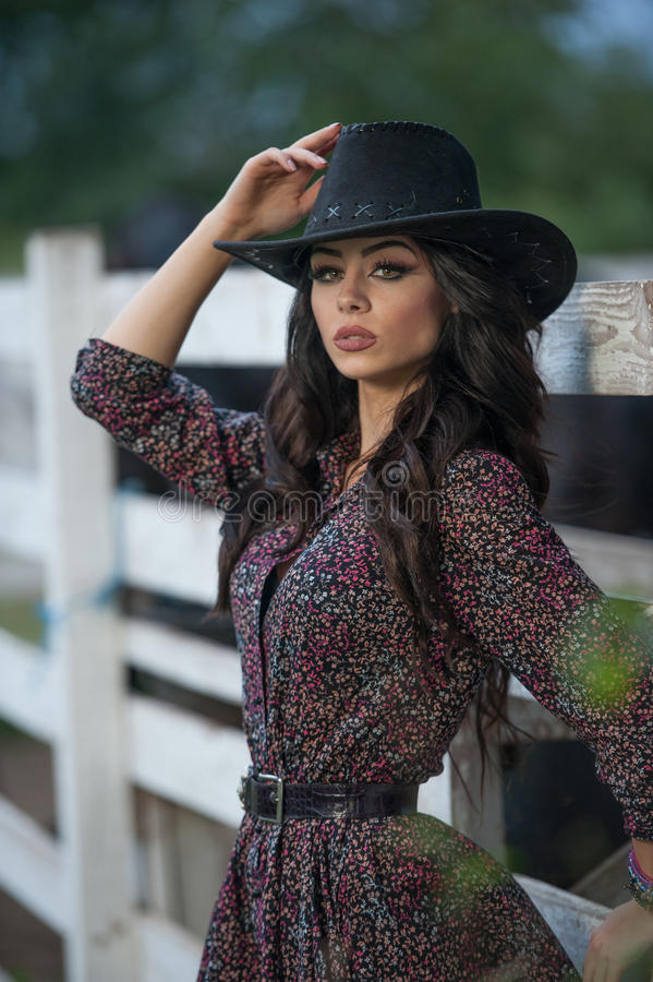 Beautiful brunette girl with country look, outdoors shot near wooden fence, rustic style. Attractive woman with cowboy hat royalty free stock photos
