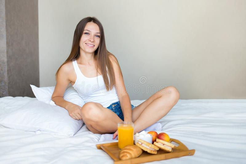 Beautiful brunette girl eating a healthy breakfast in bed and smiling stock photography