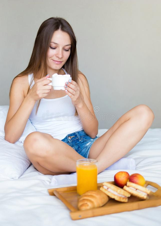 Beautiful brunette girl eating a healthy breakfast and drinking coffee in bed royalty free stock photo