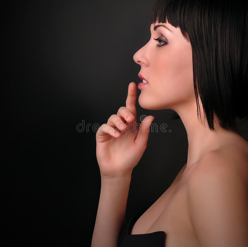 Beautiful Brunette Girl. Fashion portrait. Side vi. Beautiful Young Woman touching her lips on a black background stock photo