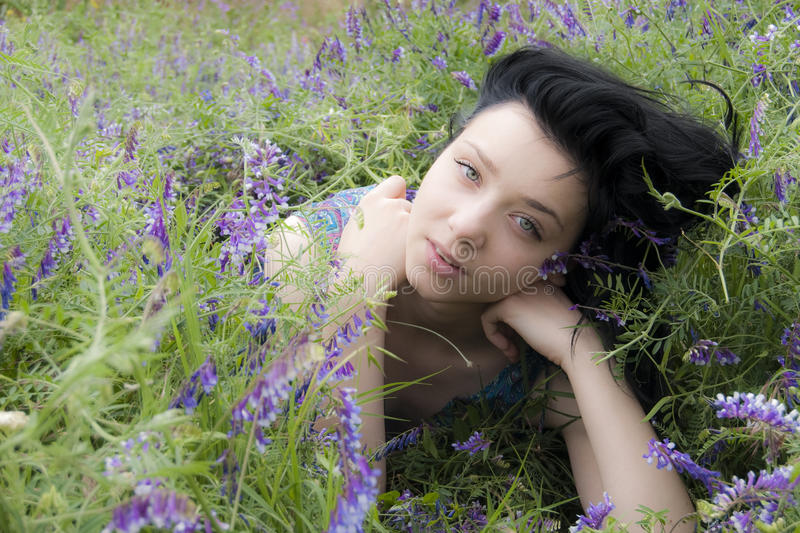 Beautiful Brunette Girl in flowers royalty free stock photography