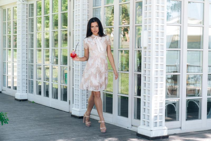 Beautiful brunette girl with glass of lemonade posing in beige colour dress outside cafe near a wooden and glass wall stock photos