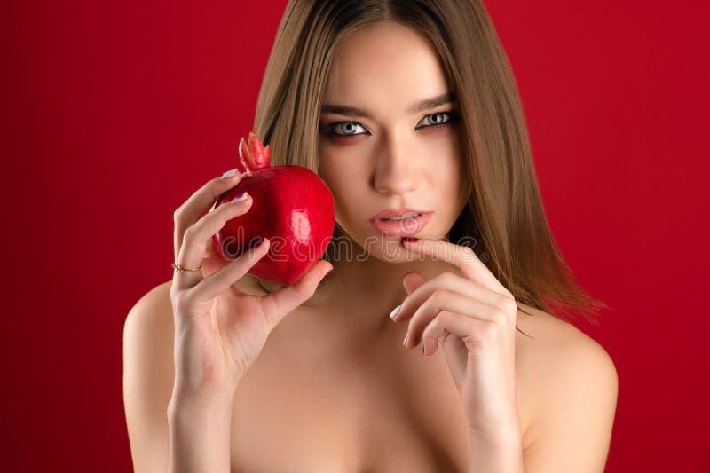 Beautiful brunette girl holding pomegranate in hand stock photo