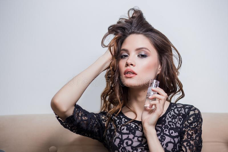 Beautiful brunette girl keeps on hand a tube of cosmetics, lifting the hair with one hand, professional makeup, close-up royalty free stock images