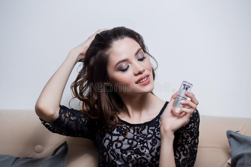Beautiful brunette girl keeps on hand a tube of cosmetics, lifting the hair with one hand, professional makeup, close-up royalty free stock image