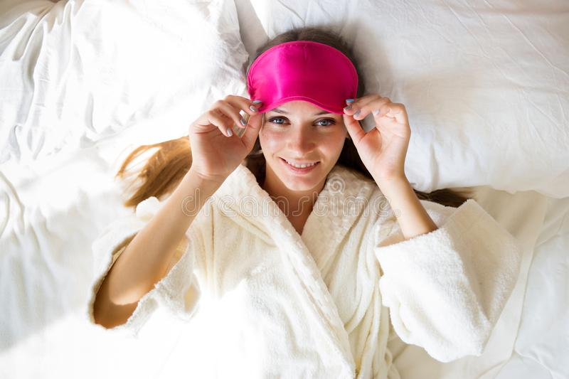Beautiful brunette girl lies in bed in a mask for sleep. She just woke up. royalty free stock images