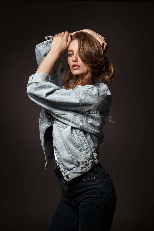 Beautiful brunette girl with long flowing hair dressed in jeans jacket and jeans poses holding her hands on her head on stock photo