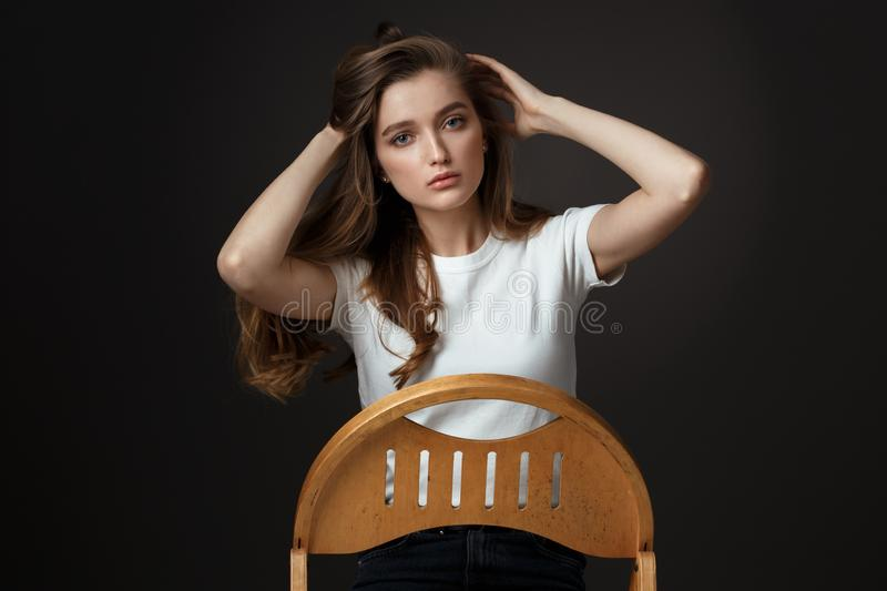 Beautiful brunette girl with long flowing hair dressed in white t-shirt and jeans poses sitting on the wooden chair on royalty free stock photo