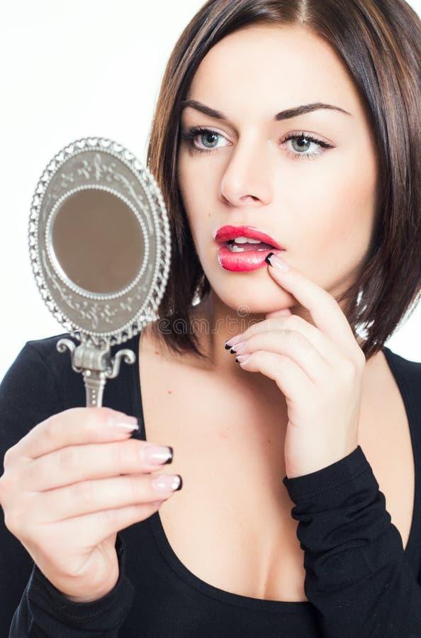 Beautiful brunette girl looks in mirror