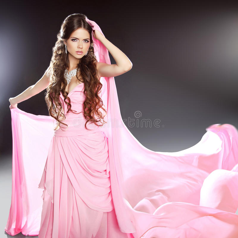 Beautiful brunette girl model in blowing transparent chiffon dress. Long wavy hair styling. royalty free stock images