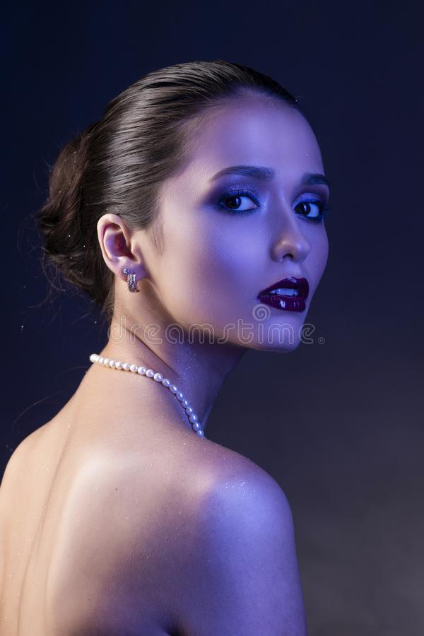 Beautiful brunette girl with naked shoulders and dark red lips m. Ake-up, wearing earrings and a pearl necklace, illuminated in blue. Conceptual low key photo stock photo