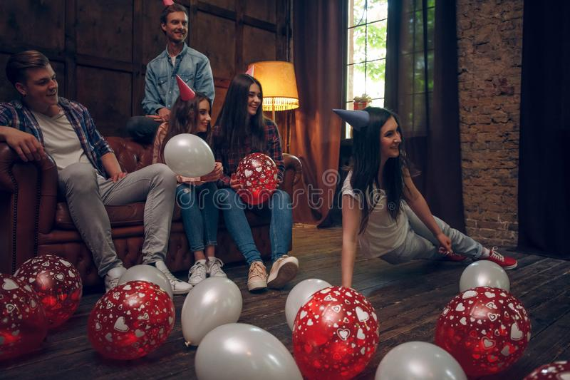 Smiling friends hanging out playing charades at birthday party stock images