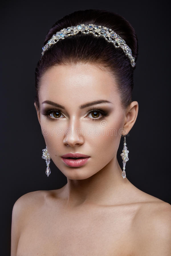Beautiful brunette girl with perfect skin, evening make-up, wedding hairstyle and accessories. Beauty face. Beautiful brunette girl with perfect skin, evening stock photo