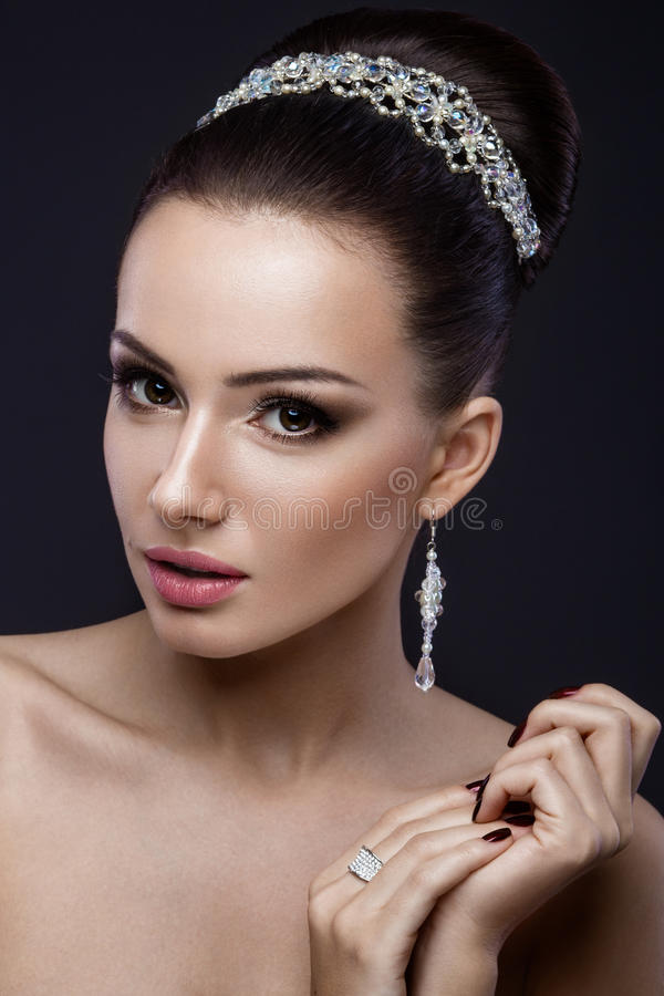 Beautiful brunette girl with perfect skin, evening make-up, wedding hairstyle and accessories. Beauty face. Beautiful brunette girl with perfect skin, evening stock photography