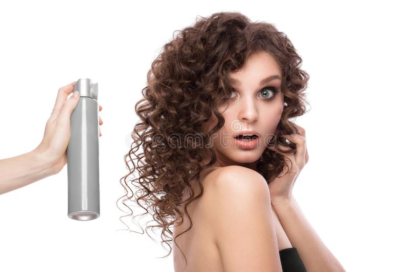 Beautiful brunette girl with a perfectly curly hair with spray bottle, and classic make-up. Beauty face. Picture taken in the studio on white background royalty free stock photography