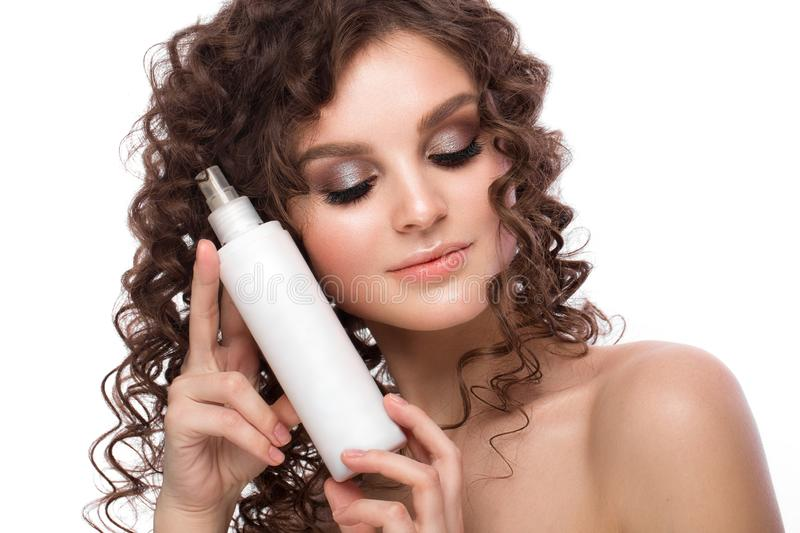 Beautiful brunette girl with a perfectly curly hair with spray bottle, and classic make-up. Beauty face. Picture taken in the studio on white background stock photos