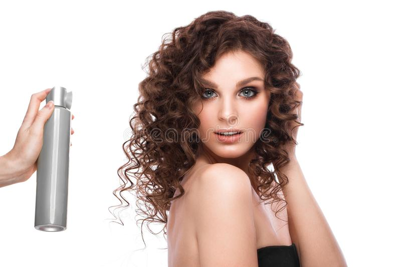 Beautiful brunette girl with a perfectly curly hair with spray bottle, and classic make-up. Beauty face. Picture taken in the studio on white background royalty free stock images