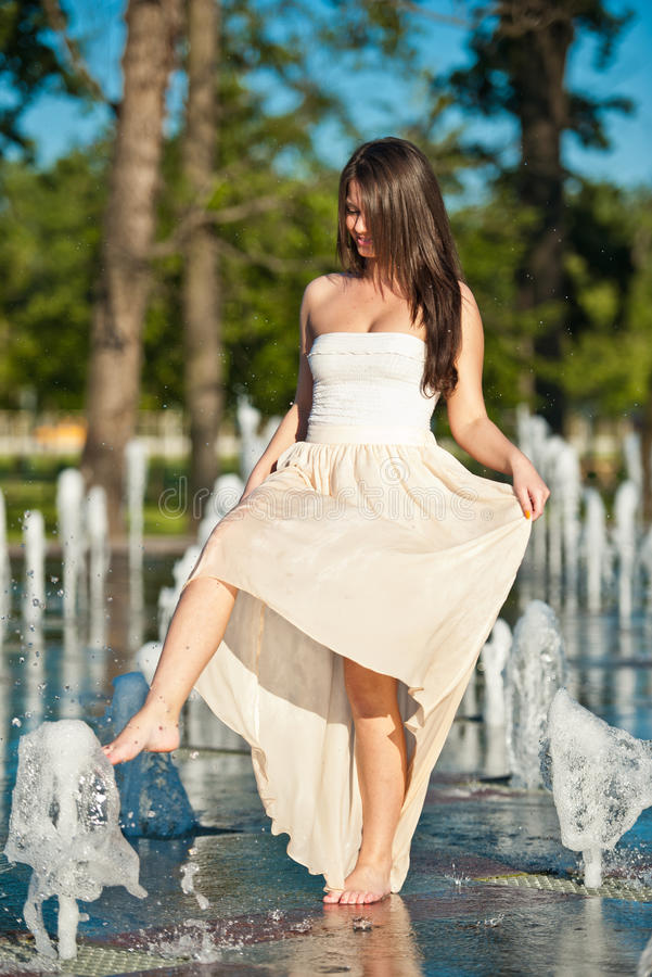 Download Beautiful Brunette Girl Playing At  Water Fountain Stock Photo - Image: 25395948