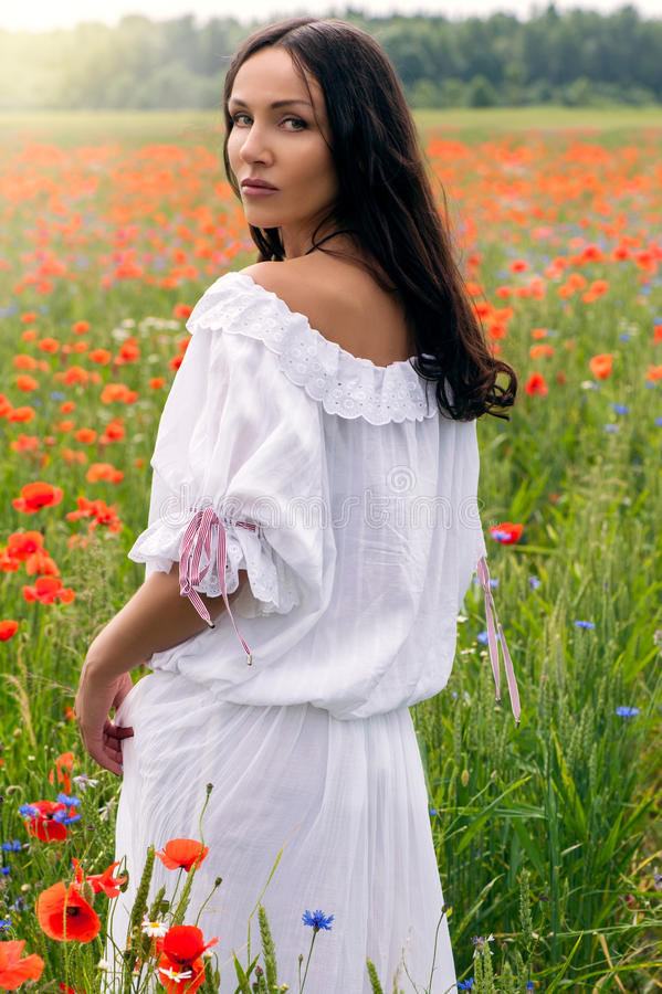 Beautiful brunette girl in poppy filed stock image