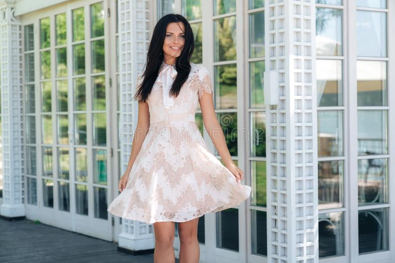 Beautiful brunette girl posing in beige colour dress outside cafe near a wooden and glass wall stock images