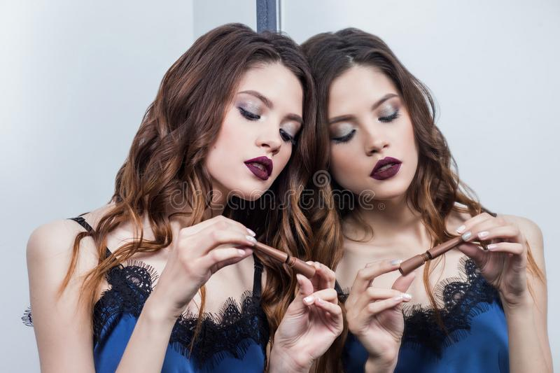 Beautiful brunette girl with professional make-up, dark Burgundy lips, stands near the mirror, looks at eyeliner, keep on hand royalty free stock photography