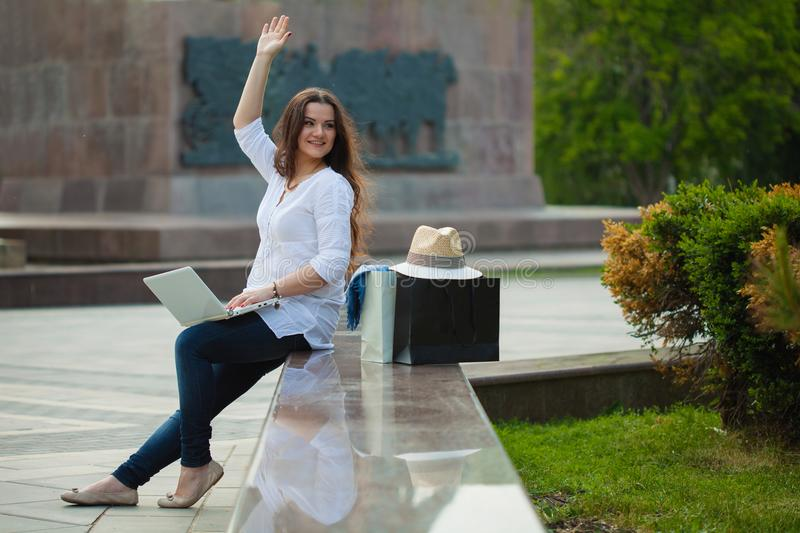 Beautiful brunette girl is sitting on the street with a laptop and shopping. She waves her hand stock photo
