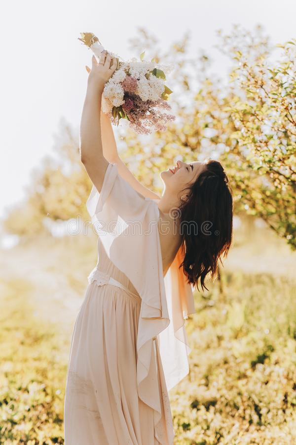 Beautiful girl standing in an apple garden and sniffing a bouquet stock photos