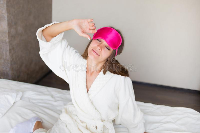 Beautiful brunette girl stretching in bed in a mask for sleeping. She just woke up. Morning Concept. royalty free stock photos